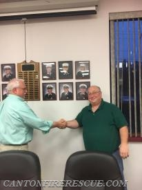 Past Chief Dalton congratulates outgoing Chief Crowe after placing his photo in the Wall of Past Chiefs.
