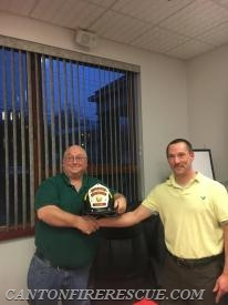 Incoming Chief Brian McCluskey presents outgoing Chief Bob Crowe with his Past Chief helmet.